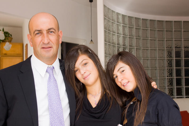 Family gathering. Father and two daughters hug together stock photography
