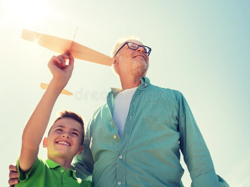 Senior man and boy with toy airplane over sky stock image