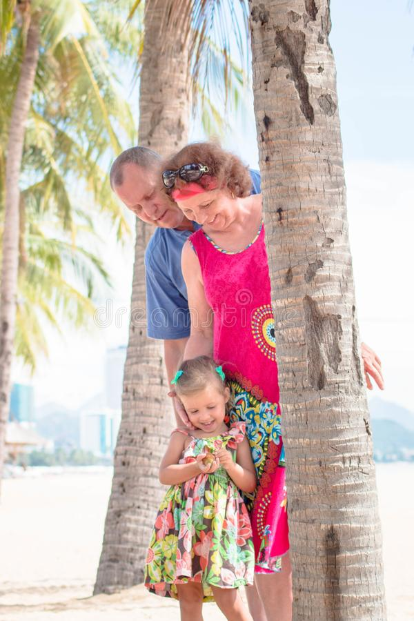 Family, generation - happy smiling grandmother, grandfather and little stand near the palm on the beach. Family, generation and people concept - happy smiling royalty free stock image
