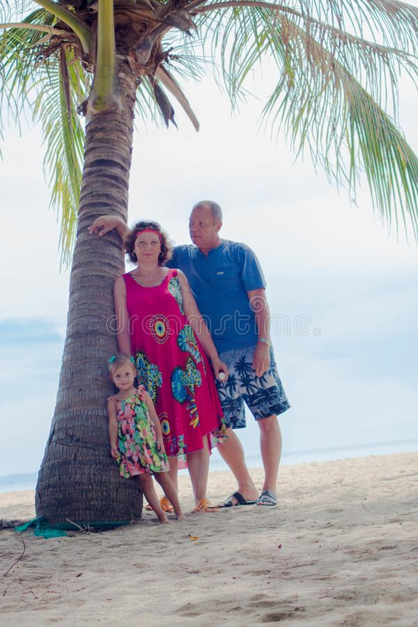 Family, generation - happy smiling grandmother, grandfather and little stand near the palm on the beach. Family, generation and people concept - happy smiling royalty free stock photo