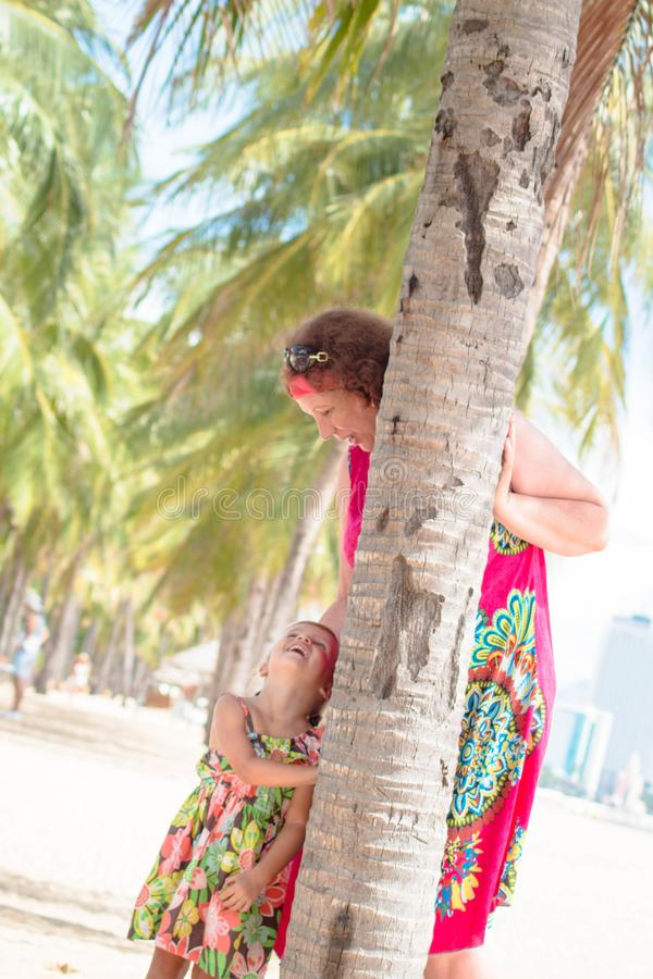 Family, generation - happy smiling grandmother and little granddaughter stand near the palm on the beach.  stock photo