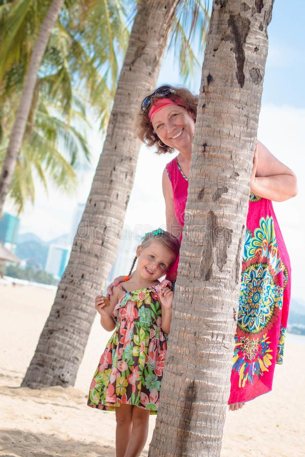 Family, generation - happy smiling grandmother and little granddaughter stand near the palm on the beach.  stock images
