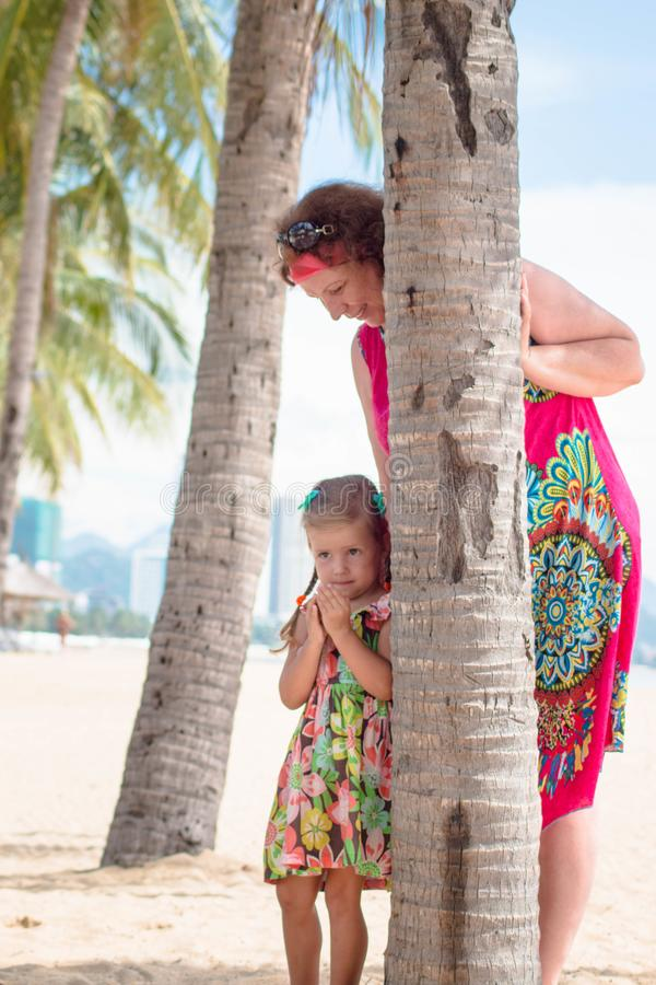 Family, generation - happy smiling grandmother and little granddaughter stand near the palm on the beach.  stock photography