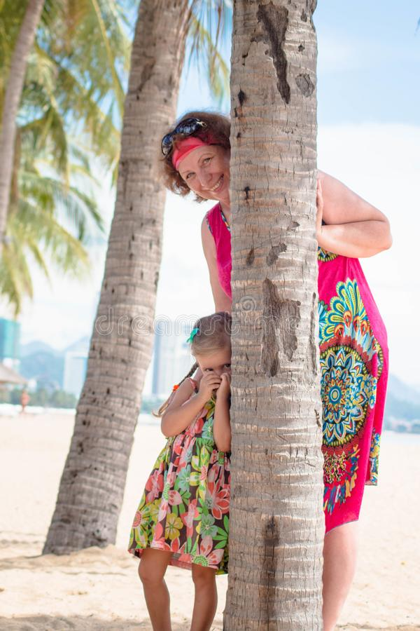 Family, generation - happy smiling grandmother and little granddaughter stand near the palm on the beach.  stock image