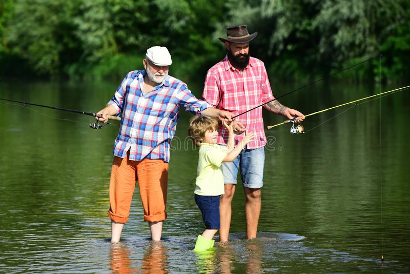 Family generation and people concept. Father teaching son how to fly-fish in river. Man in different ages. stock photos