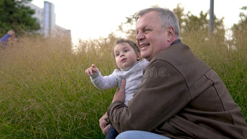 Happy smiling grandfather and little cute granddaughter at park. Family, generation and people concept - happy smiling grandfather with little cute granddaughter stock image