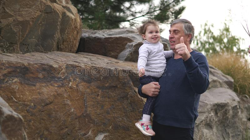 Happy smiling grandfather and little cute granddaughter at park. Family, generation and people concept - happy smiling grandfather with thumb up and little cute royalty free stock photos