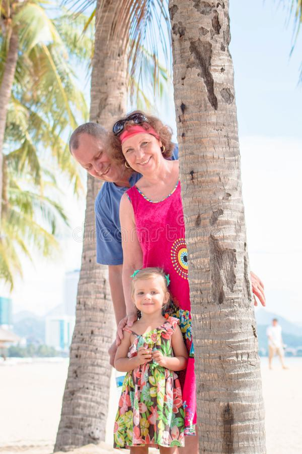 Family, generation - happy smiling grandmother, grandfather and little stand near the palm on the beach. Family, generation and people concept - happy smiling stock image
