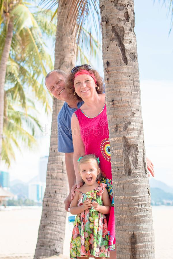 Family, generation - happy smiling grandmother, grandfather and little stand near the palm on the beach. Family, generation and people concept - happy smiling royalty free stock images