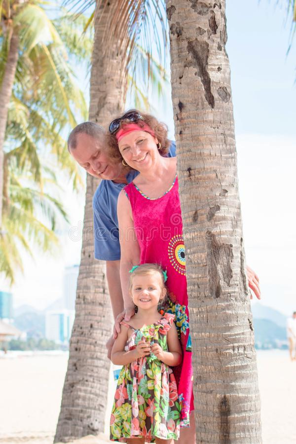 Family, generation - happy smiling grandmother, grandfather and little stand near the palm on the beach. Family, generation and people concept - happy smiling royalty free stock photos