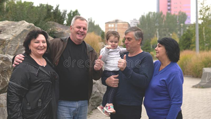 Happy smiling grandmothers, grandfathers and little granddaughter at park. Family, generation and people concept - happy smiling grandmothers, grandfathers and royalty free stock photography
