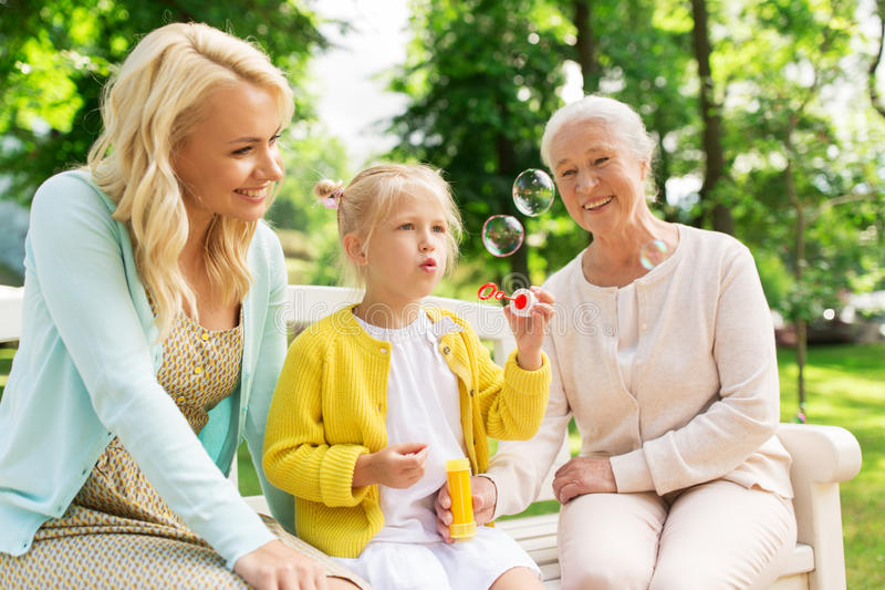 Happy family blowing soap bubbles at park stock image