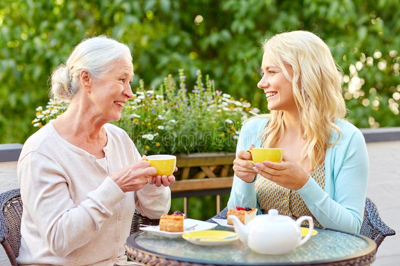 Daughter with senior mother drinking tea at cafe stock image