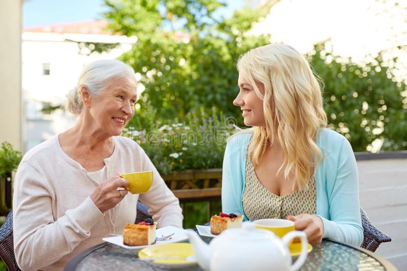 Daughter with senior mother drinking tea at cafe royalty free stock images