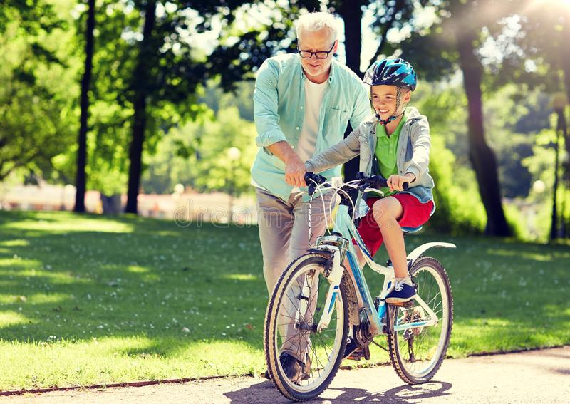 Grandfather and boy with bicycle at summer park royalty free stock photo