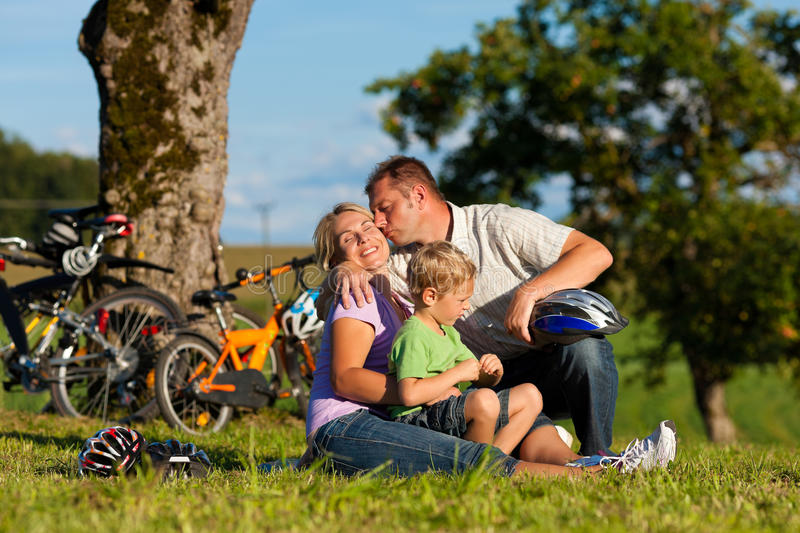 Family on getaway with bikes. Happy family (father, mother and son) on getaway with bikes - they have a break stock photos