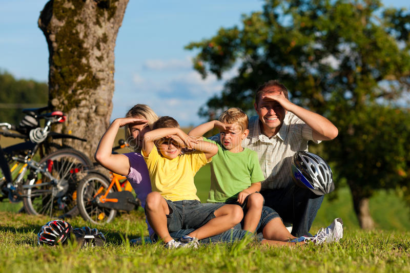Family on getaway with bikes. Happy family (father, mother and two sons) on getaway with bikes - they have a break stock photography