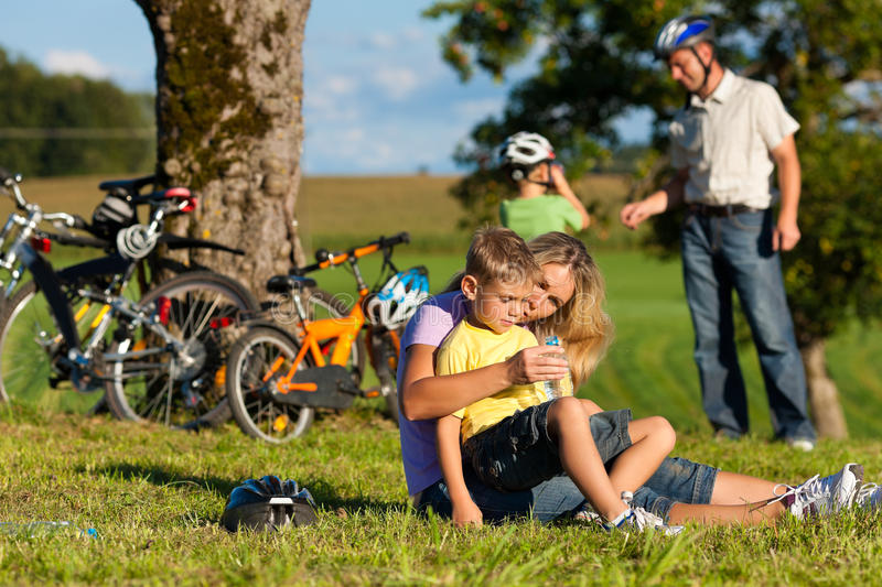Family on getaway with bikes. Happy family (father, mother and two sons) on getaway with bikes - they have a break royalty free stock photos
