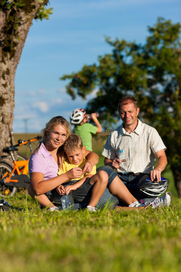 Family on getaway with bikes. Happy family (father, mother and two sons) on getaway with bikes - they have a break stock image