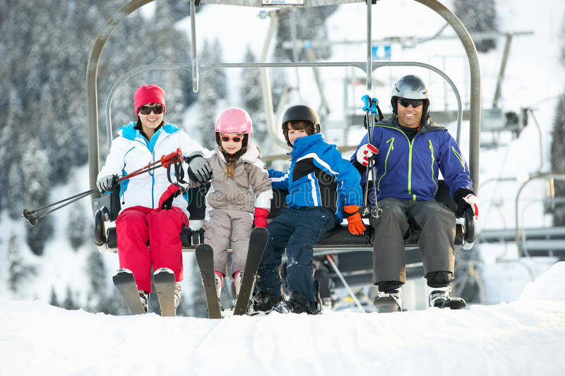 Family Getting Off Chair Lift On Holiday. Family Getting Off chair Lift On Ski Holiday In Mountains royalty free stock images