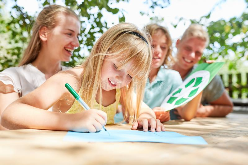 Family and girl while drawing. And brother holding recycle logo royalty free stock photo