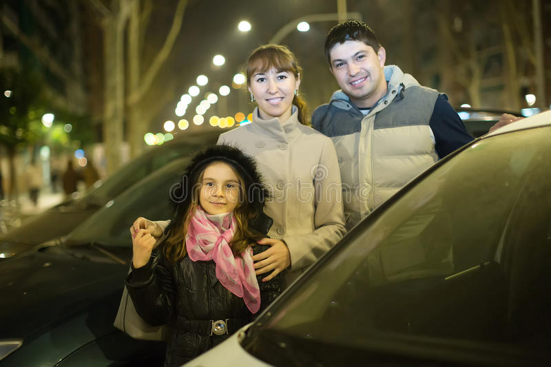 Family with girl posing near car outdoors in winter stock images