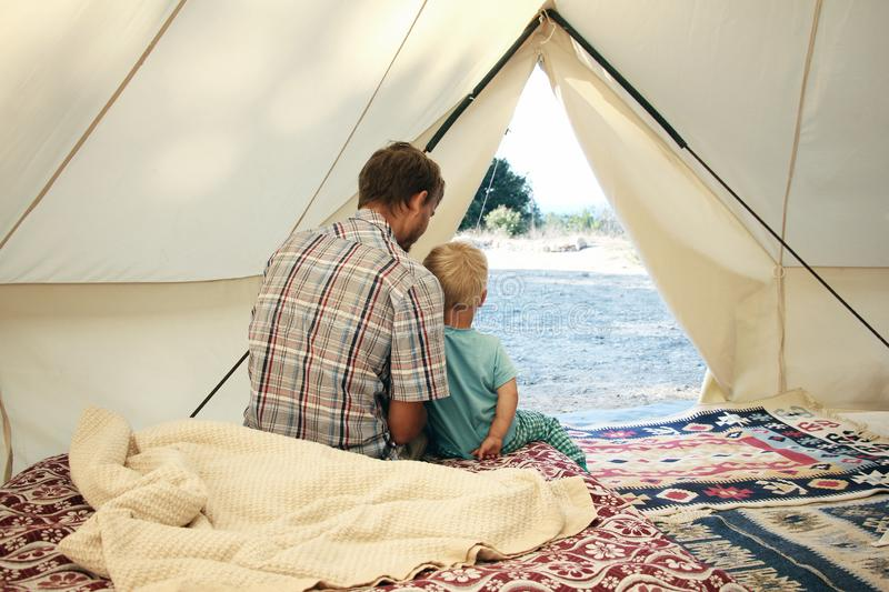 Family glamping. Father and his toddler son inside big camping tent with cozy interior. Luxury travel accomodation into the forest stock images