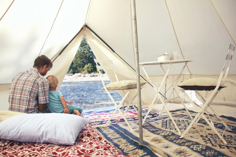 Family glamping outdoor vacation. Father and his toddler son inside big camping tent with cozy interior. Luxury travel royalty free stock photography