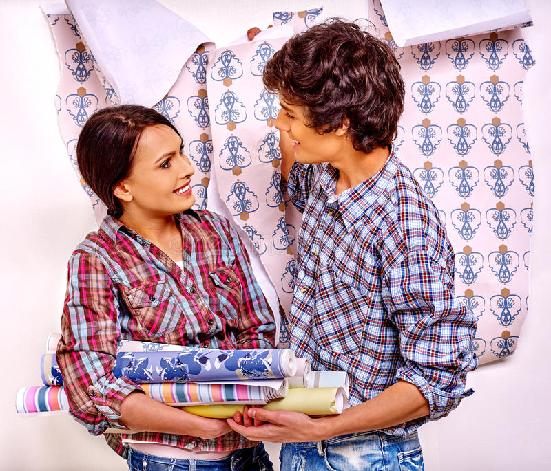 Family glues wallpaper at home. Happy family wallpaper glues and debate at home royalty free stock images