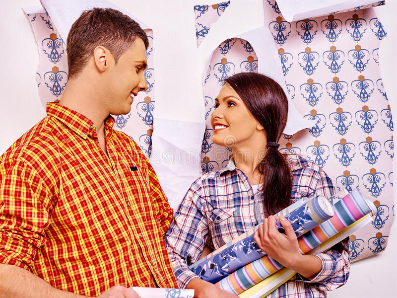 Family glues wallpaper at home. Happy young family choice and glues wallpaper at home royalty free stock images