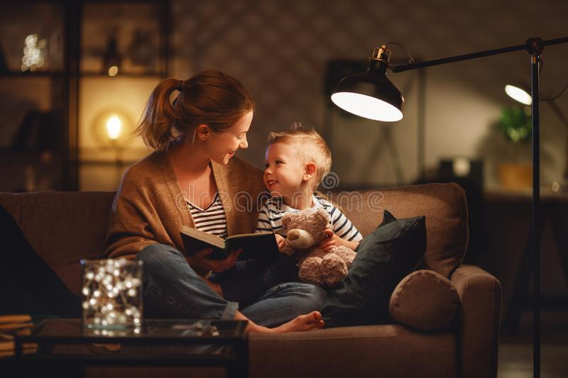 Family before going to bed mother reads to her child son book near a lamp in evening royalty free stock images
