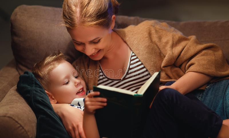 Family before going to bed mother reads to her child son book near a lamp stock images