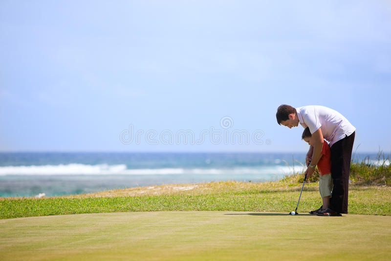 Family golf. Father teaching his son to play golf