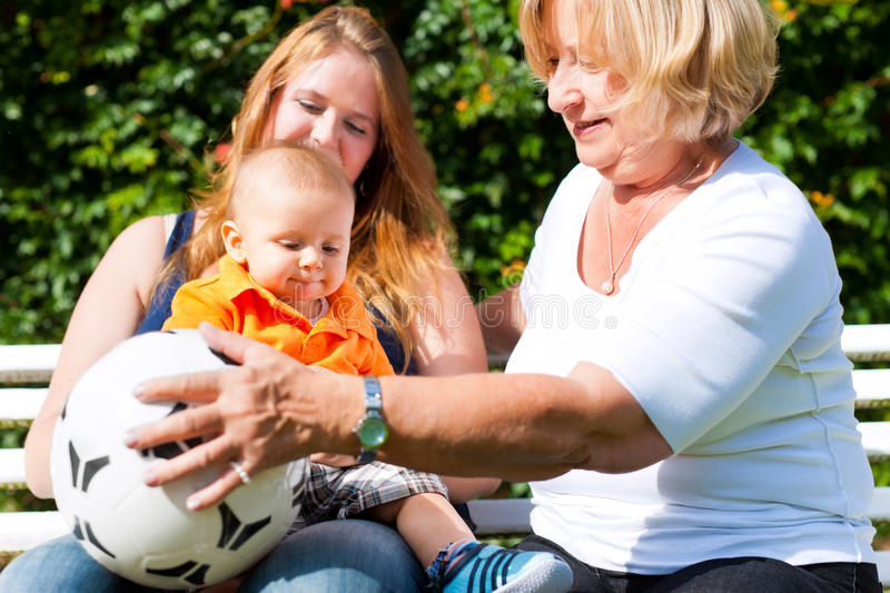 Family - Grandmother, mother and child in garden. Family - Grandmother, mother and child sitting and playing with a football in garden royalty free stock photo