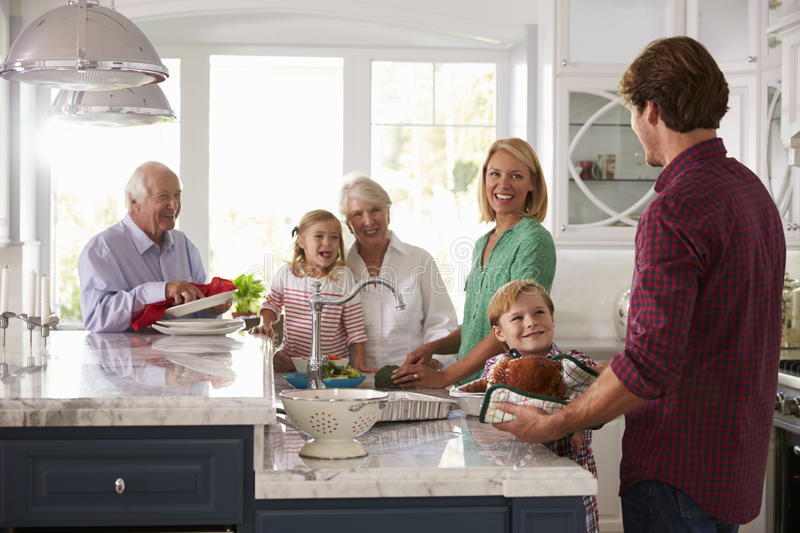 Family With Grandparents Make Roast Turkey Meal In Kitchen stock photo