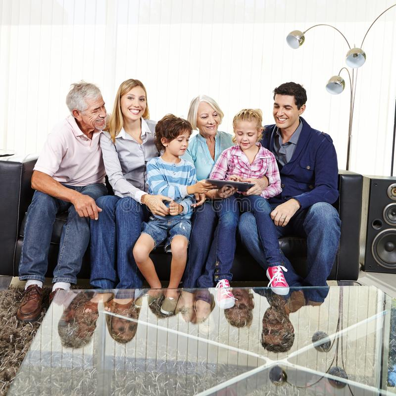 Family with grandparents and tablet computer stock image