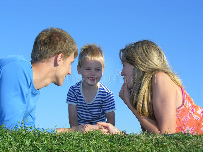 Family on grass faces. On blue sky royalty free stock photography