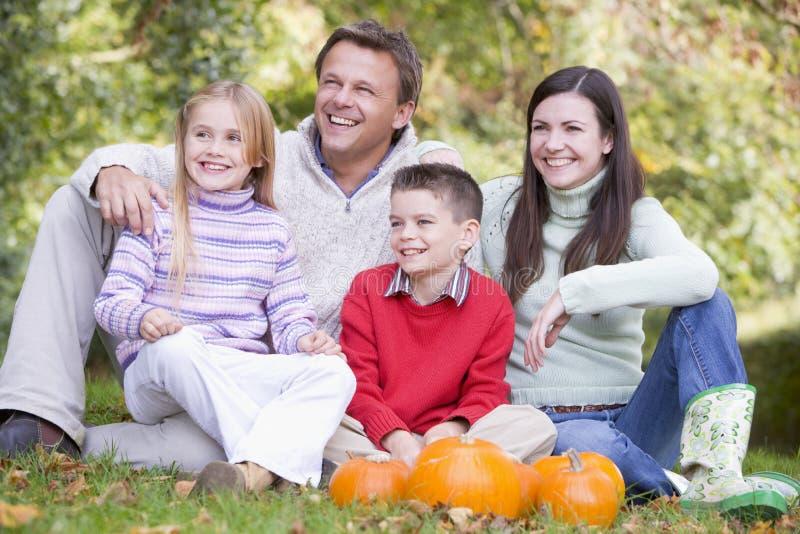 family grass pumpkins sitting smiling στοκ εικόνα με δικαίωμα ελεύθερης χρήσης