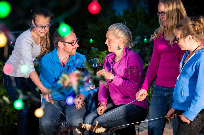 Family grilling bread on a stick at barbeque. In garden at nighttime stock photography