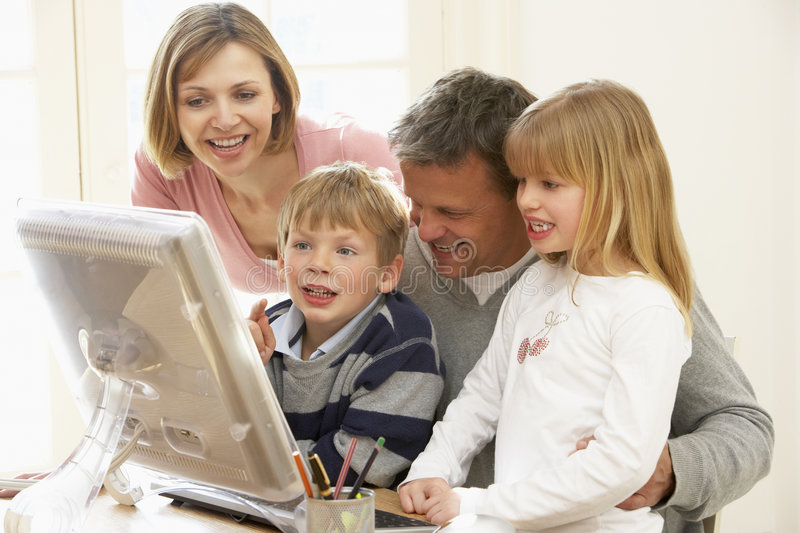 Family Group Using Computer Together Stock Photo