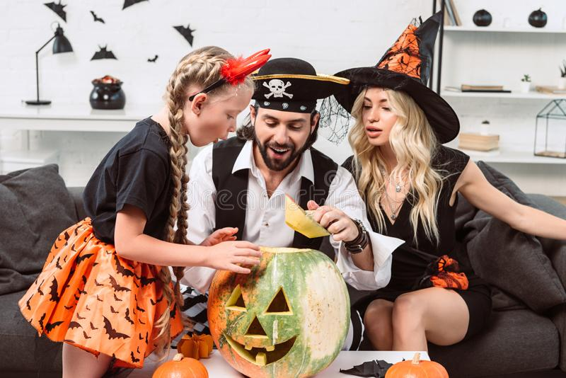 family in halloween costumes on sofa at coffee table with pumpkins stock photography