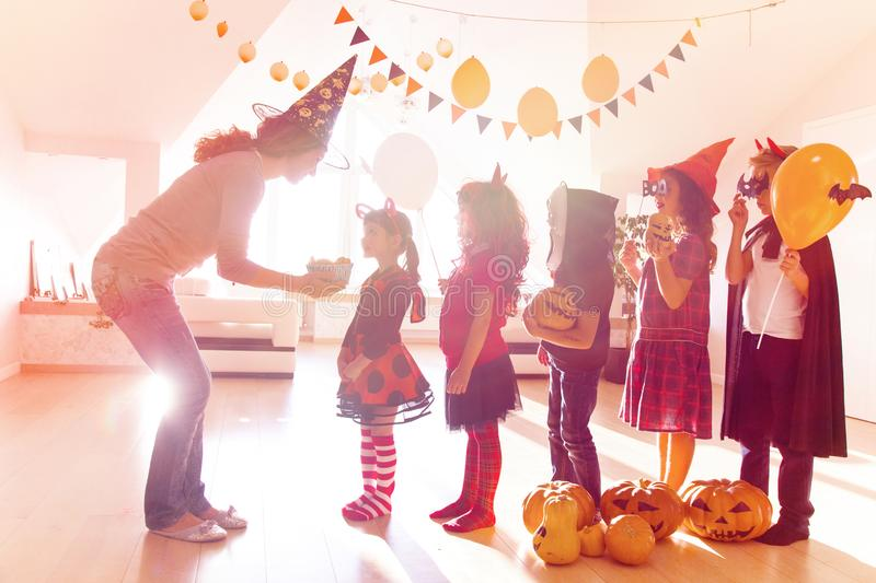 Family in Halloween party. Merry kids ask for a treat for a Halloween party royalty free stock image