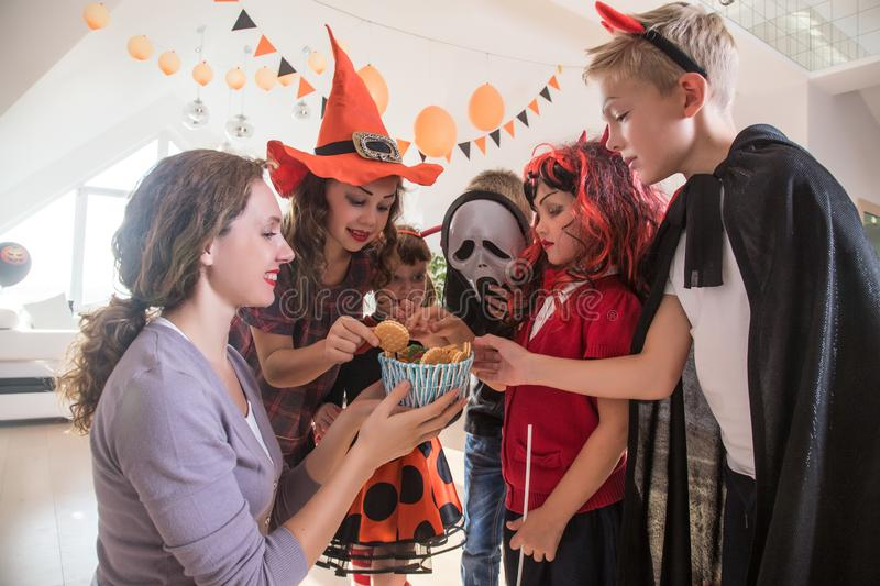 Family in Halloween party. Merry kids ask for a treat for a Halloween party stock image