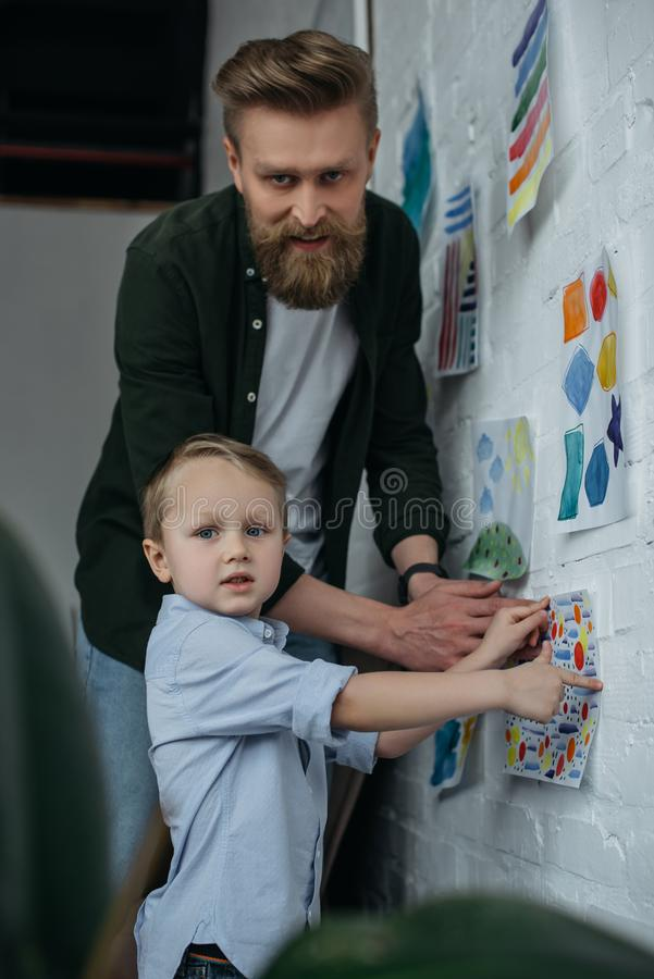 Family hanging childish drawing on wall together. At home stock images