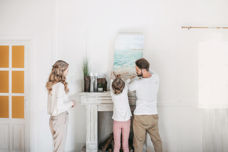 Family hanging picture of sea over the fireplace at home. Happy family hanging picture of sea over the fireplace at home stock images