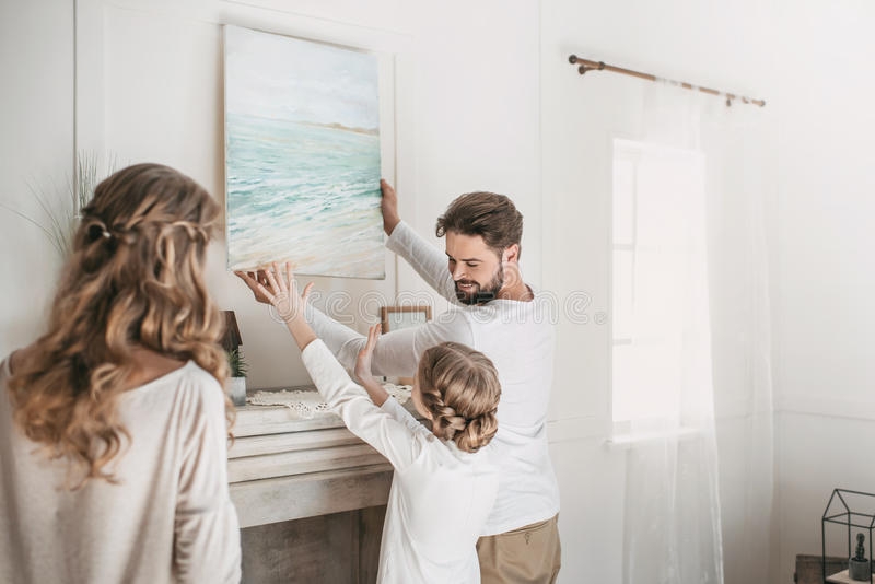 Family hanging picture of sea over the fireplace at home. Happy family hanging picture of sea over the fireplace at home royalty free stock photo