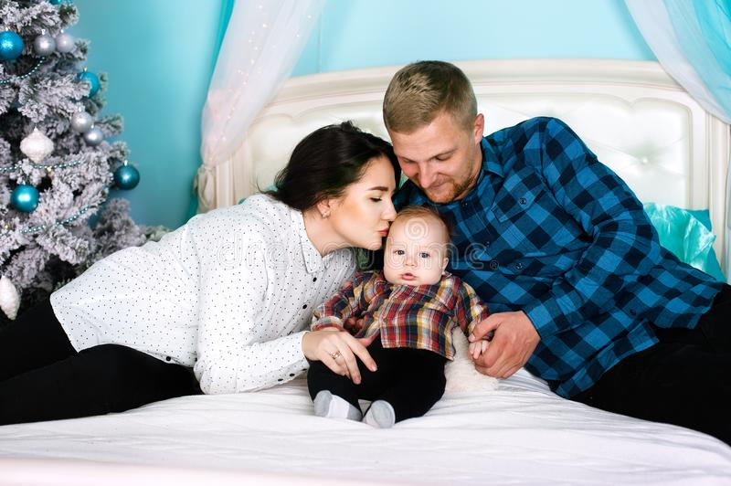 Family happiness - parents kiss their newborn baby at a Christmas tree royalty free stock photography