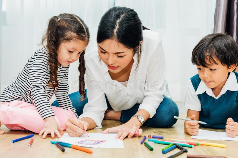 Family happy child kid girl kindergarten paint drawing on peper teacher education with mother mom stock photo