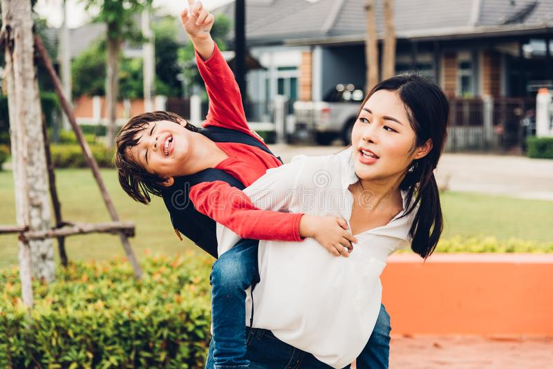 Family happy children kid son boy kindergarten playing ride back. Piggyback mother mom on outdoors park stock photography