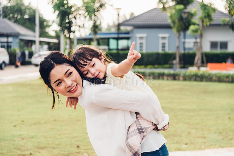 Family happy children kid son girl kindergarten playing ride back piggyback mother mom. On outdoors park royalty free stock images